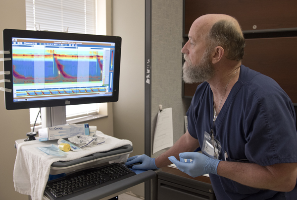 Phillips looks at images that show the pressure of a patient's swallowing motions.