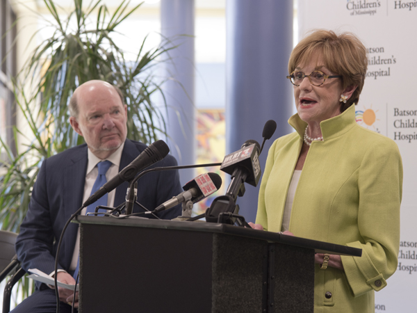 Joe Sanderson watches as Kathy speaks during the April press conference held in the lobby of the Children's Hospital to announce the fund-raising campaign.