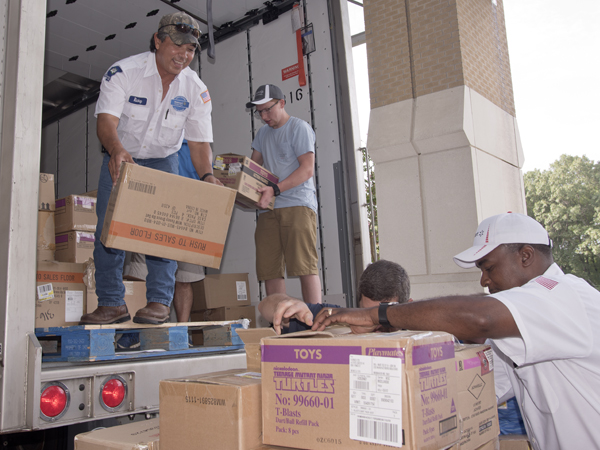 Walmart employee Rickey Oliver and volunteer Joseph Miller pass down boxes, unload truckloads of donated toys.