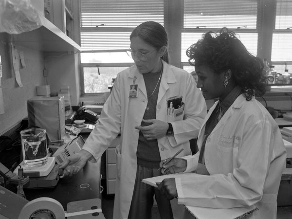 Jerlen Young, right, a member of one of the early Base Pair classes in 1992-1993, works with her mentor and longtime Base Pair leader, Dr. Donna Sullivan.
