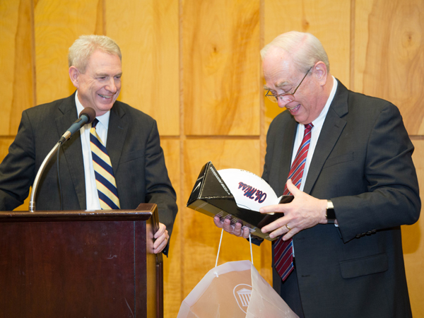 "Jones watches as Thigpen, an avid Ole Miss fan, opens a gift from the University of Mississippi's ""top official,"" a football signed by football coach Hugh Freeze."