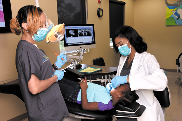 Minor, right, receives assistance from Kara Lindsey in Minor's Pearl clinic, Smile Design Orthodontics.