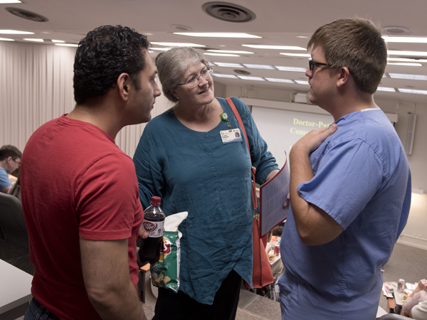 Schlessinger introduces herself to Dr. Sohiel Khoshroo, left, an anesthesiology resident, and neurosurgery resident Dr. Zachary Smalley during an orientation session for new Medical Center residents in June.