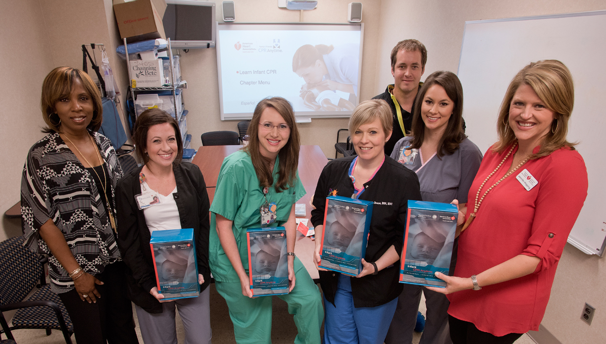 The American Heart Association is donating about a year's supply of infant CPR kits to UMMC to use in training parents in classes. Showing a few of the more than 1,100 kits are, from left, American Heart Association Community Health Director Rosa Wilson, nurses Erin Jones, Ashley Stegall, Amanda Bourne, Billy Needham and Emily Thompson, and Jennifer Hopping, vice president of the Greater Southeast Affiliate of the American Heart Association.