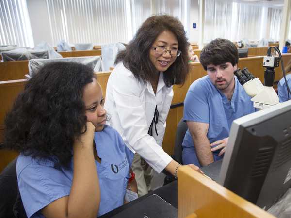 Bailey, left, and her lab partner Austin Henderson, right, are schooled in histology by Dr. Dongmei Cui.