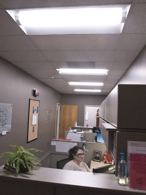 Donna Bridges, administrative assistant in the School of Medicine, is bathed in the brilliance of LED lighting at her desk in the Clinical Sciences Building.
