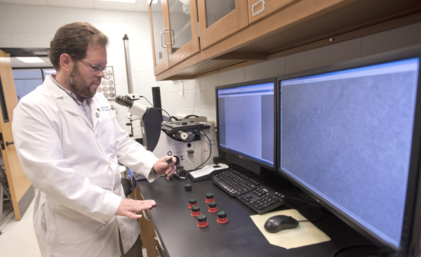 Dr. Michael Roach examines metallic microstructures in his laboratory.