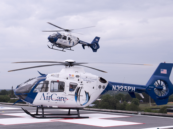 AirCare 3 sits on the helipad atop UMMC's Conerly Critical Care Hospital as AirCare 2 departs.