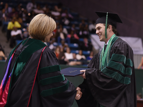 Zachary Johnson of Ocean Springs receives his Doctor of Medicine from Dr. LouAnn Woodward, vice chancellor for health affairs and dean of the School of Medicine.