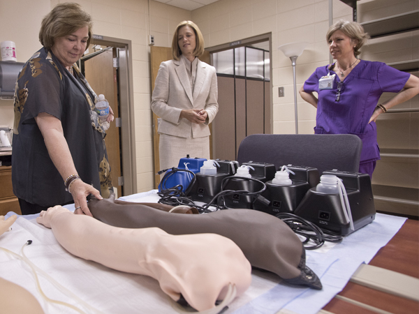 Dr. Kim Hoover, dean of the School of Nursing, center, spent the morning touring Vandergriff, left, through the school, including a stop in the simulation lab where MacSorely, right, demonstrated advances in simulation equipment such as the artificial arms students use to practice starting I.V. fluids.