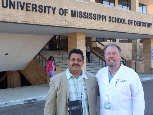 Dr. Raphael Samos, left, the senior dental surgeon for the country of Belize, stands with Ramsey in front of the School of Dentistry.