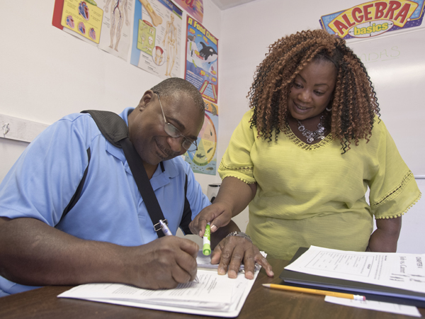 Kimberly Knight, education coordinator for GED classes at the Prosperity Center of Greater Jackson, checks Battle's work.