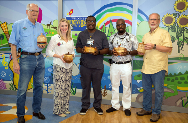 Magnolia Woodturners Gerald Lawrence, left, and Michael Frazier, right, show some of their bowls for Beads of Courage. Receiving the donation are, from second from left, social worker Melissa Underwood, respiratory therapist Jacolby Anderson and Dr. David Josey, assistant director of the CF center at Batson Children's Hospital.