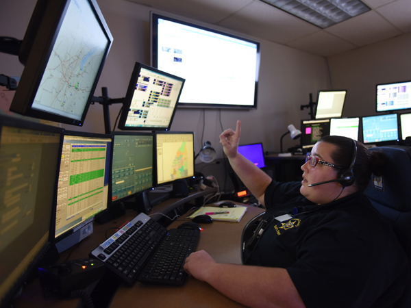 Melissa Swope, a shift sergeant at the Rankin County Sheriff's Department, prepares to answer 911 calls as she communicates with first responders.