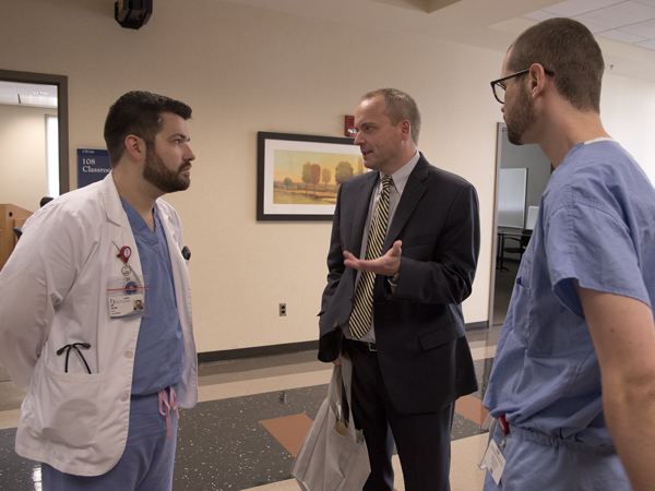 Prior to his address Wednesday for the Gay-Straight Alliance Lunch Lecture Series, Rob Hill, center, is welcomed by medical students Ian Taylor, left, GSA co-president, and Jimbo Dickerson.