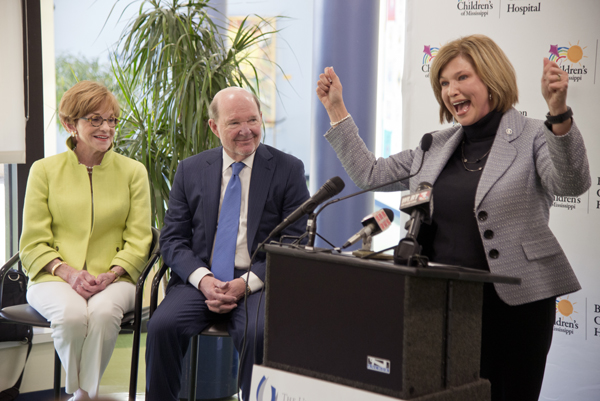 Dr. LouAnn Woodward, UMMC vice chancellor for health affairs and dean of the School of Medicine, cheers at the announcement of a $10 million gift to Children's of Mississippi by Joe and Kathy Sanderson, looking on.