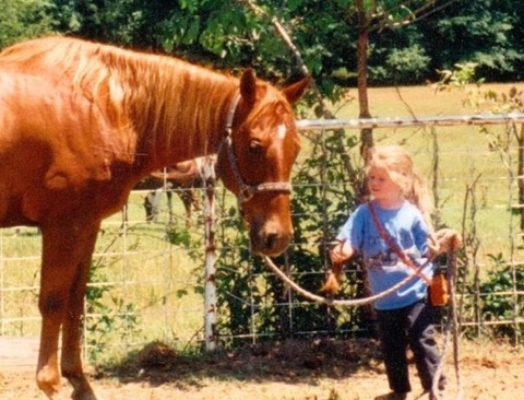 Dean, approximately 3 or 4 years old, holds the reins of her very first horse, Cowboy. Cowboy passed away on Monday, April 10.