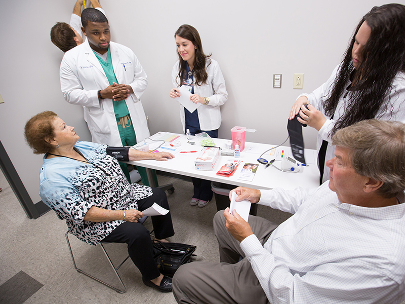 Belzoni residents Wilma Thomas, seated left, and Bill Allen, seated right, take advantage of a free health screening at the new Community Care Clinic.