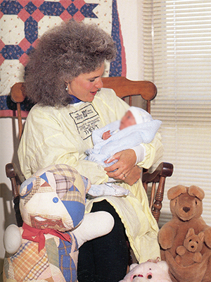 Rockin' Mamas project chair Pat Ammons rocks a NICU patient in 1989.