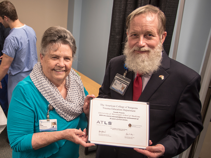 Kay Watkins, program administrator of the Division of Continuing Health Professional Education; and Dr. Greg Timberlake, an ATLS instructor and professor emeritus, hold the certificate recognizing UMMC's trauma life support training program for 30 years of operation.