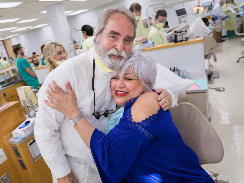 Dr. David Felton, dean of the School of Dentistry, gets a hug from Sellers in appreciation for her new dentures.