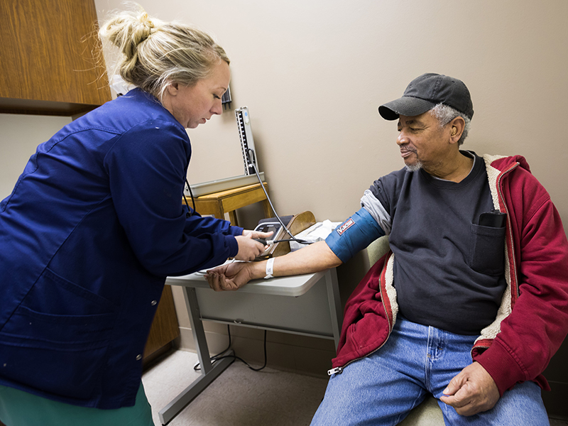 Brittany Groover, licensed practical nurse, takes patient John Hall's blood pressure.
