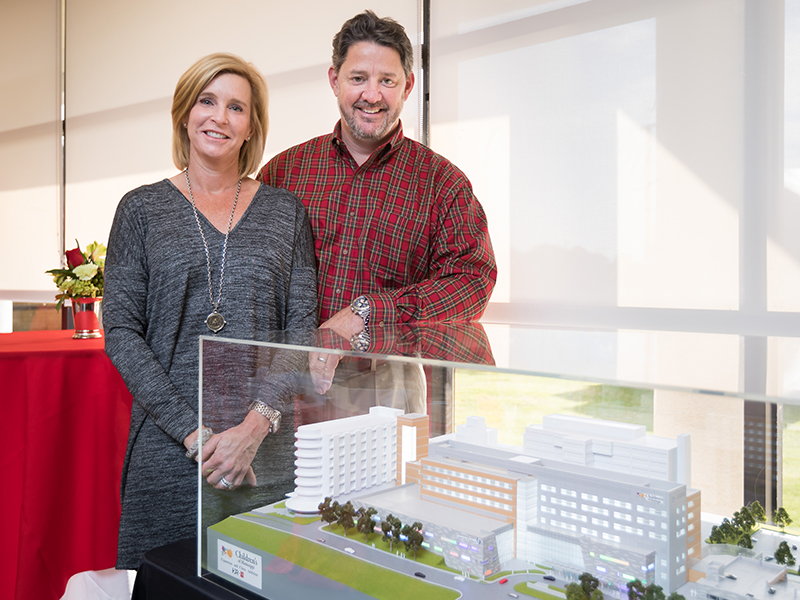 Priscilla and Dave O'Donnell show where their gift to the Campaign for Children's of Mississippi is going -- to help fund construction of a new children's tower, shown here in model form.
