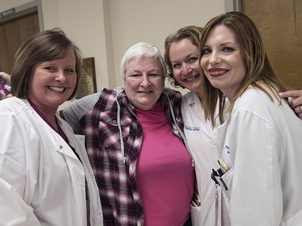 Celebrating the end of cancer treatment for Hinton (in pink) are oncology nurse Nikki Simmons; Dr. Barbara Craft, associate professor of medical oncology; and Dr. Natale Sheehan, assistant professor of medical oncology.