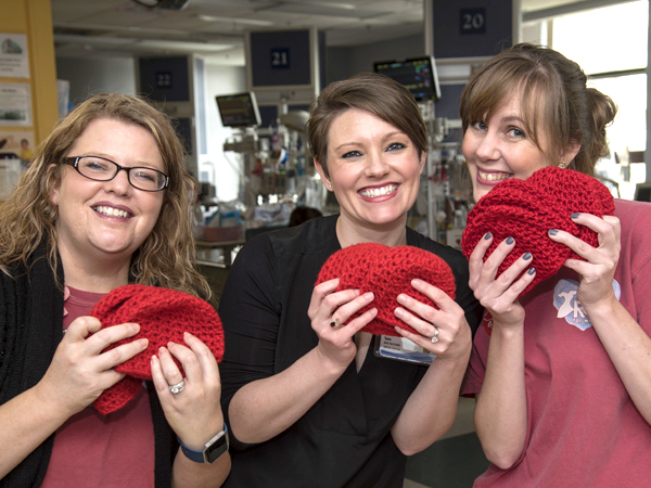 From left, executive assistant Selena Daniel of the Children's Heart Center, nurse practitioner Frannie Tynes and American Heart Association Go Red for Women director Christy Bridges show some of the many crocheted baby beanies donated for Little Hats, Big Hearts.