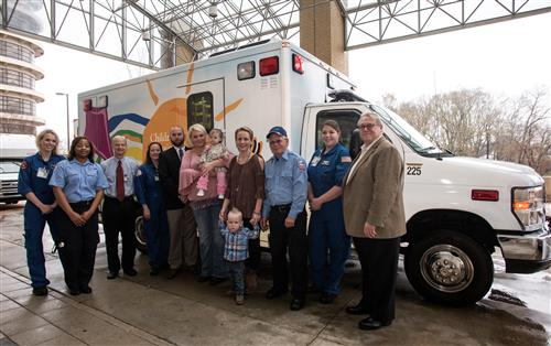 Celebrating the commissioning of a new AMR neonatal ambulance for Batson Children's Hospital are, from left, nurse Emily Jones, AMR driver Cassetta McGee, neonatal transport team medical director Dr. Kelly Hersey, nurse Kathy Hamilton, UMMC neonatal and pediatric transport manager Stephen Houck, Kristie Benson and daughter Paisley, Morgan Strickland and son Jack Reynolds, AMR driver Robert Whitley, nurse Lauren Russell and AMR public affairs manager Jim Pollard.