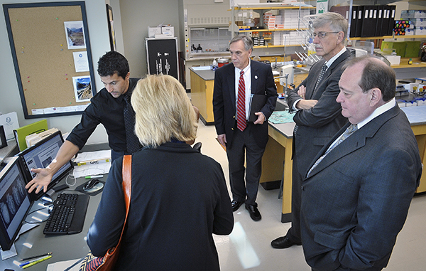 Professor of physiology and biophysics Dr. Alejandro Chade, back left, describes his research to professor and chair of physiology Dr. John Hall, center, and NIH director Dr. Francis Collins, back right, during Collins' 2012 visit to UMMC.
