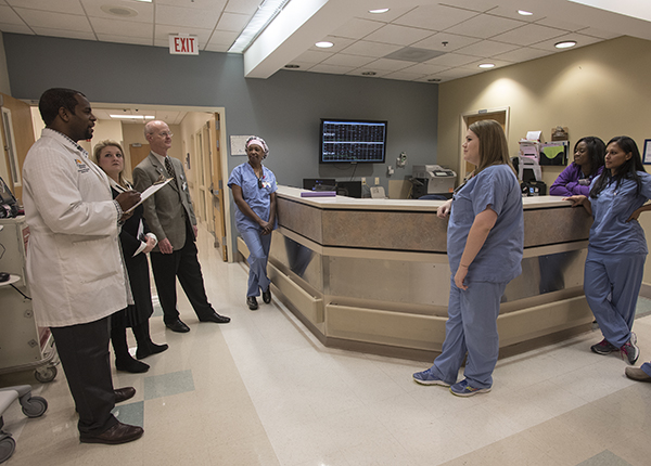 Driscoll Devaul, left, Molly Brasfield and Dr. Charles O'Mara speak with nurses and staff in labor and delivery at Wiser Hospital.