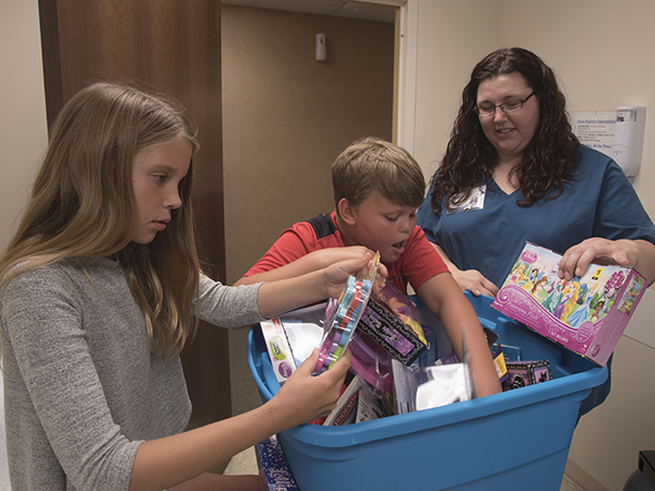 Amber Taylor, right, a licensed practical nurse at Lakeland Family Medicine, helps twins Jordyn and Justice Burgemaster of Madison choose a toy from a box from an assortment collected by Taylor.