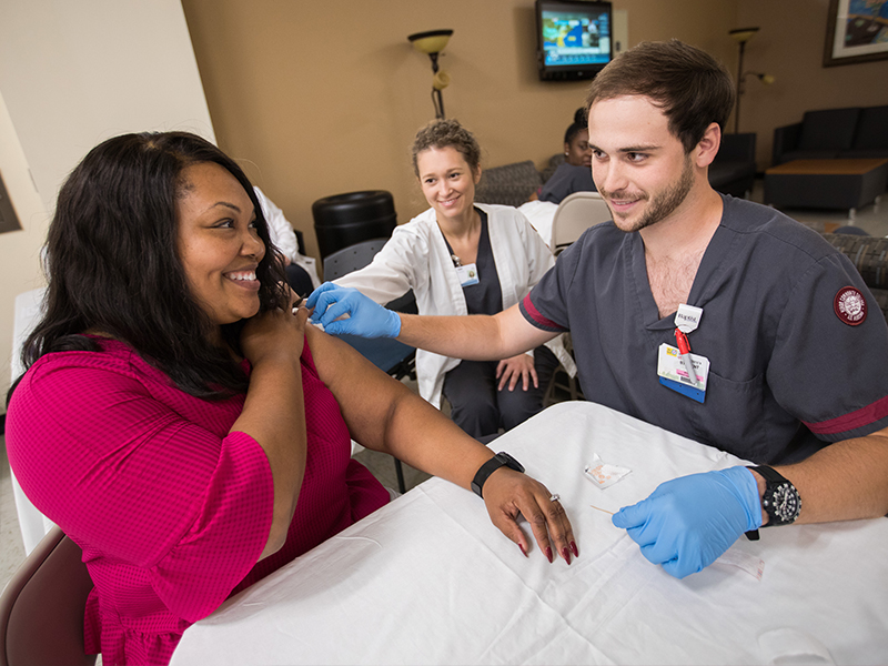Briana Thompson, UMMC accreditation specialist, receives her annual flu shot from Seth Batton, a Hinds Community College nursing student, while fellow Hinds nursing student Collins Davis looks on Oct. 23 in the Verner Holmes Learning Resource Center.