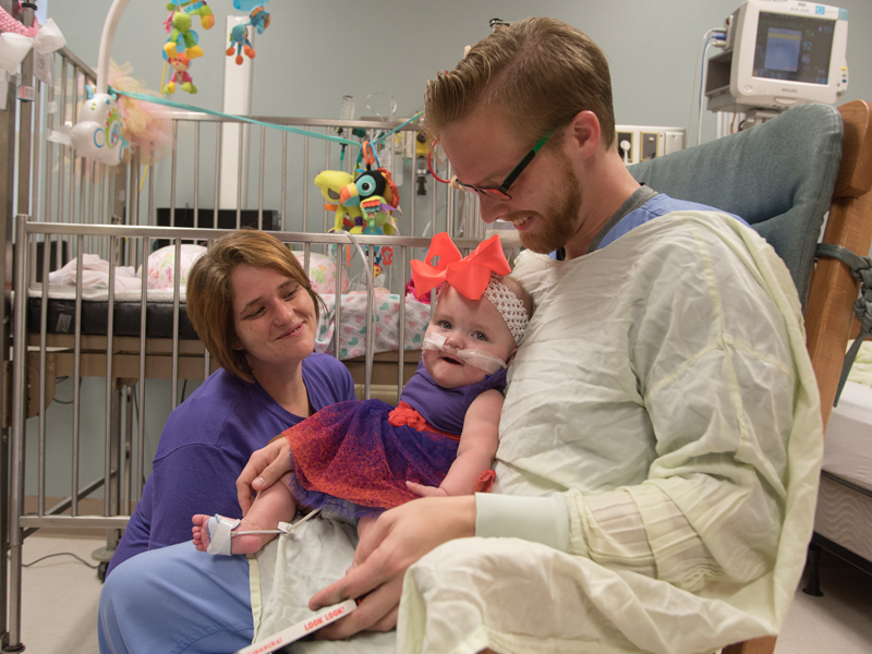 While Sonny Gunn, a second-year occupational therapy student, rocks Deavannah Bass, the infant's mother, Deanna, coaxes a smile from her toddler during the child's last day in the Neonatal Intensive Care Unit in the Winfred L. Wiser Hospital for Women and Infants.
