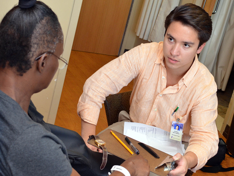 John Andrew Del Castillo, a psychometrist with Methodist Rehabilitation Center's neuropsychology department, evaluates a patient.  Del Castillo is an aspiring medical school student who has benefited from MEDCORP IV, a program of study offered by the Office of Health Careers Opportunity to students who want to improve their admissions exam scores. (Photo by Carey Miller, Methodist Rehabilitation Center)