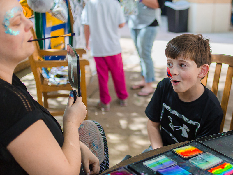 Evan Reynolds is shown his face paint by artist Emily Schmidt during a party at Batson hosted by the Mississippi Children's Museum. Ryan's sister, Emma, is a patient at Batson.