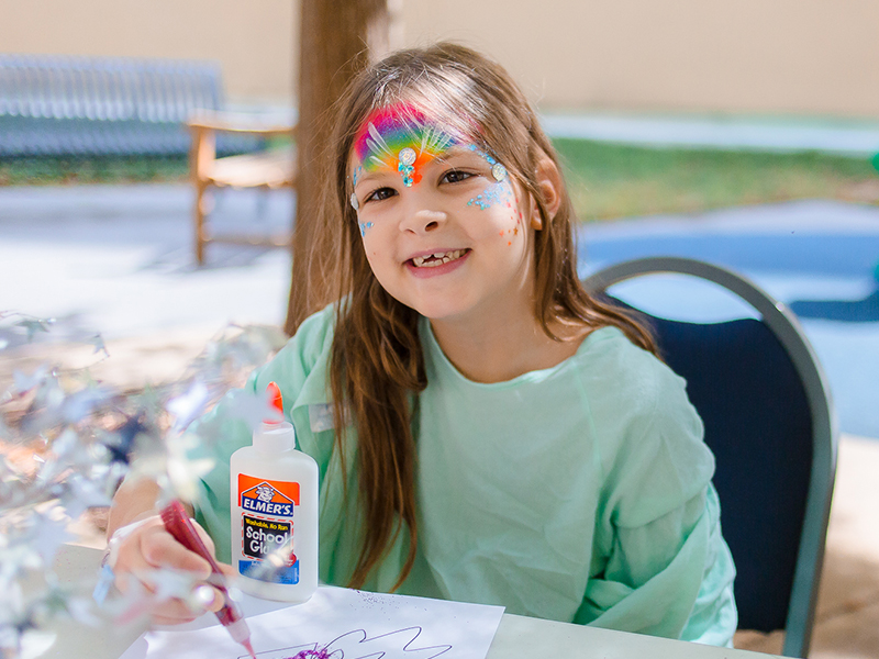 Batson Children's Hospital patient Brooklyn Cockrell of Tallulah, La., smiles as she creates rocket-inspired art during a space-themed Mississippi Children's Museum Day at the hospital.
