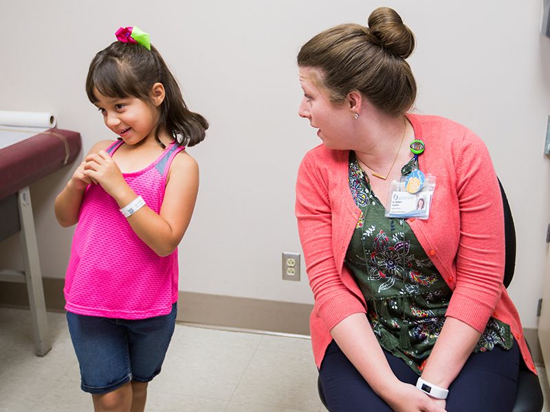 Dr. Barbara Saunders breaks the ice with her patient, Lana Puga, 6, at a UMMC child development clinic. Lana and her brother John Wesley Bishop, 4, see Saunders every four or five months, brought by their legal guardians, Pearlie and Daniel Warren, to Jackson from their home in the Mount Olive area.