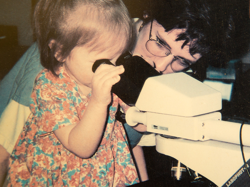 A young Paige Robinson takes a look through a microscope on an early visit to UMMC. Beside her is Anne Belue, a medical technologist for a number of years in the Children's Cancer Center who now lives in South Carolina.
