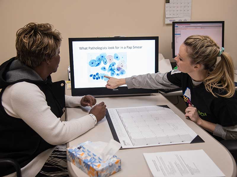 Dr. Melissa Brents, a pathology resident, reviews Pap test charts with Mangle Shanks of Jackson before showing Shanks her cervical test results at the 2017 See, Test & Treat screening.