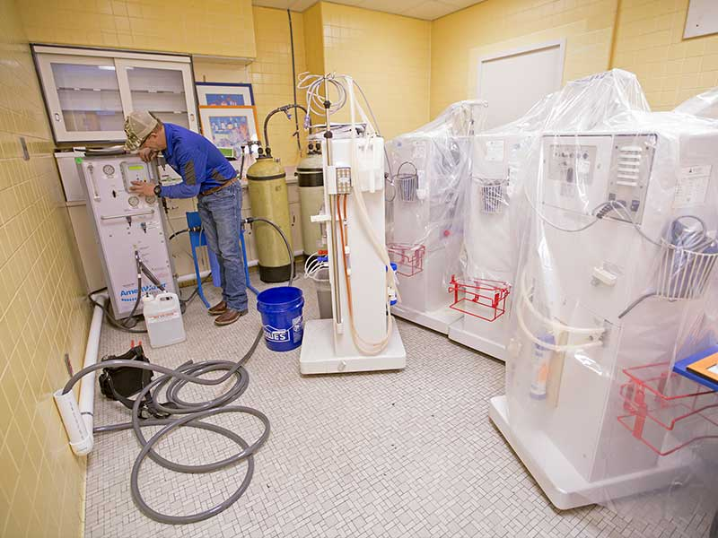 Brian Neely of Freeman Water Treatment installs temporary reverse osmosis treatment systems for a room within the Medical Center's dialysis unit that's not normally used for patient care.