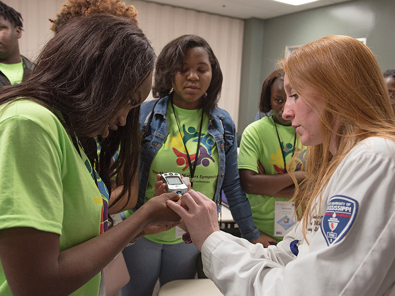 Callie Swinney, right, a fourth year pharmacy student, shows  Callaway High's Kyla Sterling how to perform a glucose test during the health fair portion of the symposium.