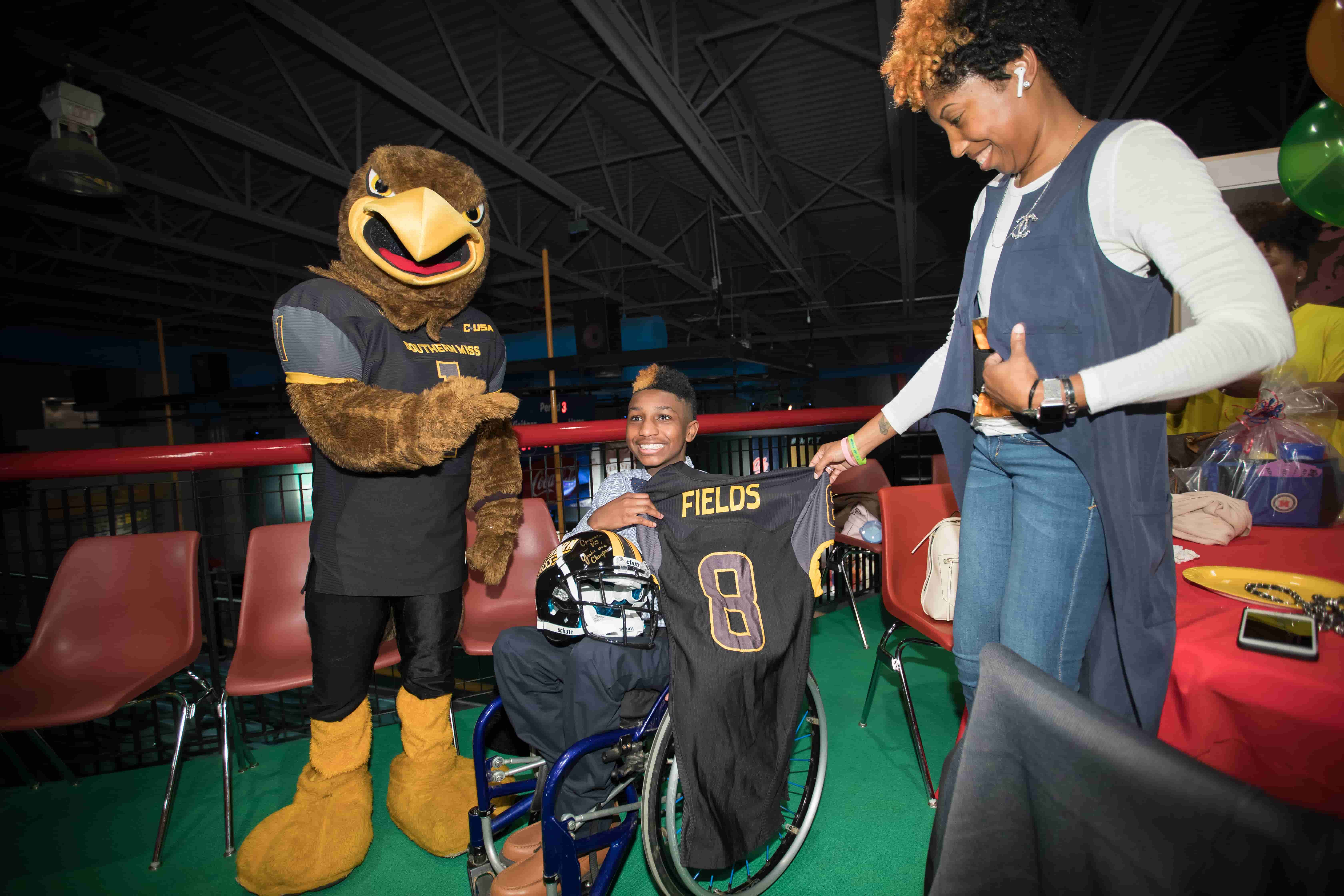 2018 Children's Miracle Network Champion KJ Fields and mom DeeWanda Fields, a University of Southern Mississippi alumna, smile with Southern Miss mascot Seymour.