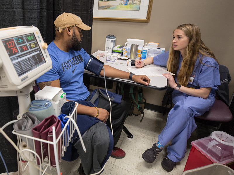 In medical triage, Lydia Nunes, a first-year medical student, takes the medical history of Treance Hobbs, of Pearl.