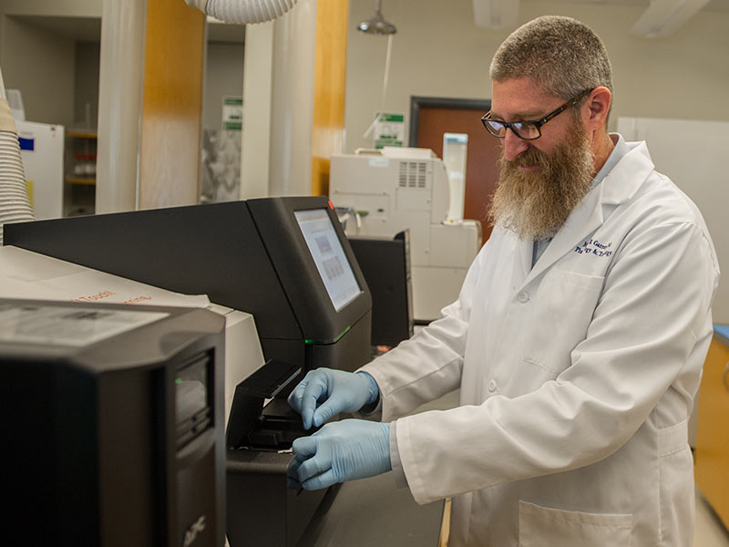 Garrett prepares to run the MGCF's MiSeq next generation sequencer.