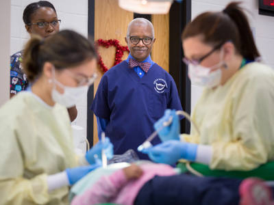 State Sen.  Hillman Frazier, center, looks on as Jolie Nguyen, left, a fourth-year dental student, and Scarlett Woods, a second-year dental student, treat Khloe Bailey, a Johnson Elementary School student.