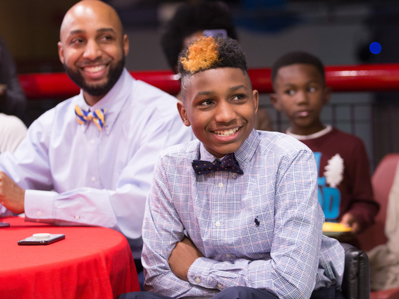 With father Kelvin Fields looking on, KJ Fields smiles as he is announced 2018 Children's Miracle Network Hospitals Champion for Mississippi.