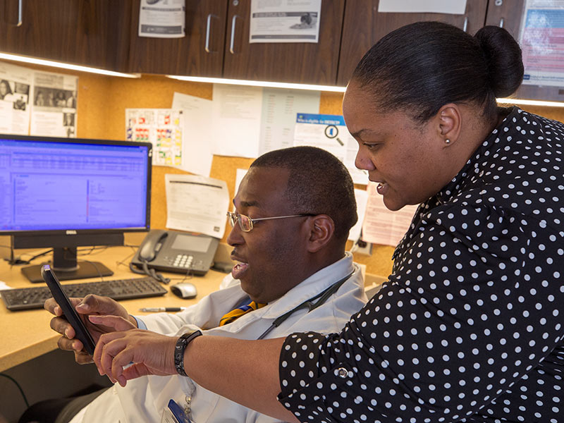 Dr. Tobe Momah, assistant professor of family medicine, reviews electronic patient information with Dr. Shannon Pittman, family medicine chair.