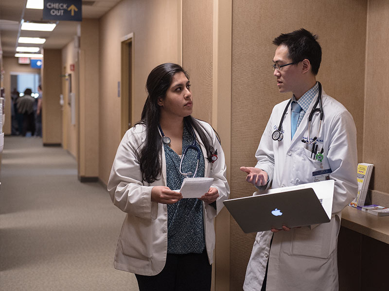 Dr. Michael Yeung-Lai-Wah consults a patient's electronic health record on his laptop as he discusses treatment with Pooja Chawla, a third-year medical student in her family medicine rotation.